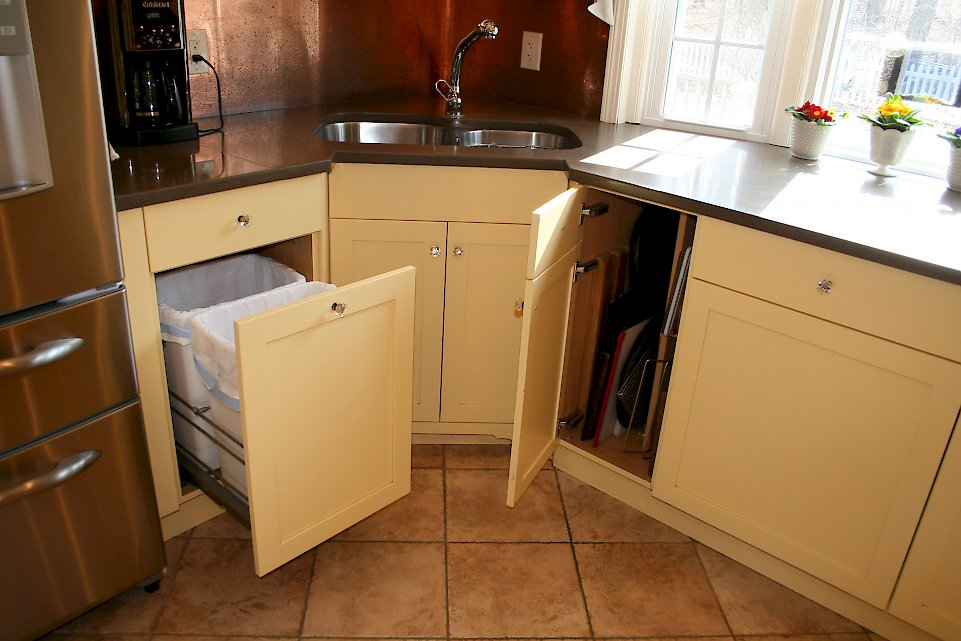 The double bin trash pull-out and cabinet for storing large pans.