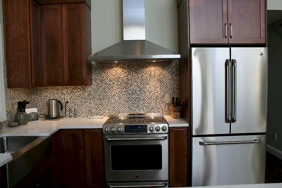 An XO brand chimney hood and GE Electric range.