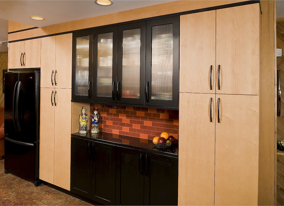 Tall pantry cabinets on the opposite side of the kitchen.
