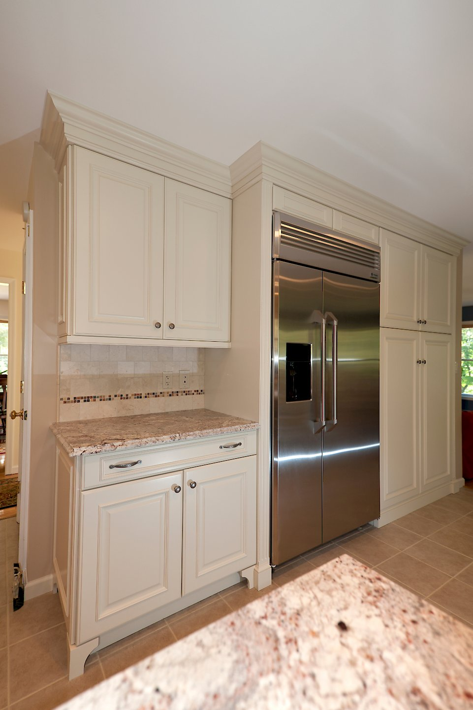 A stainless steel refrigerator with more cabinetry on the opposite wall.