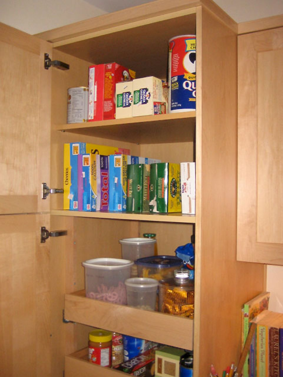 Tall pantry cabinet pull-out drawers on the bottom and regular shelving on top.