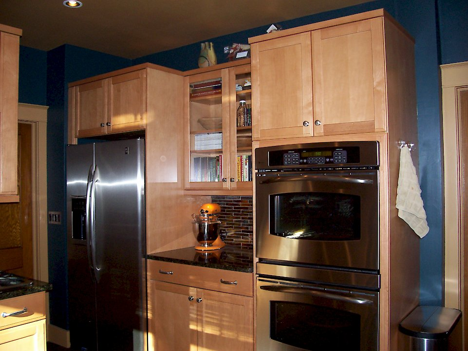 A stainless steel double oven and refrigerator.