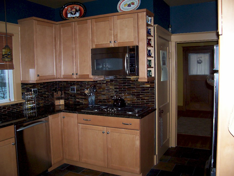 A stainless hood microwave and gas cooktop.