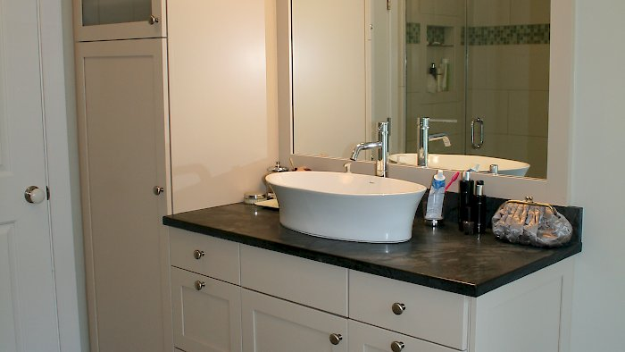 Brookhaven Vanity and tall cabinet with a vessel sink.